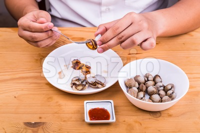 Person extracting cockles from its shell for consumption with dips Stock Photo