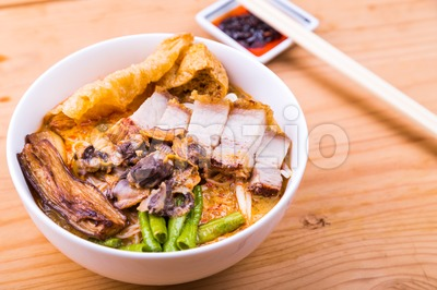 Delicious spicy curry noodle with roast pork and cockles Stock Photo