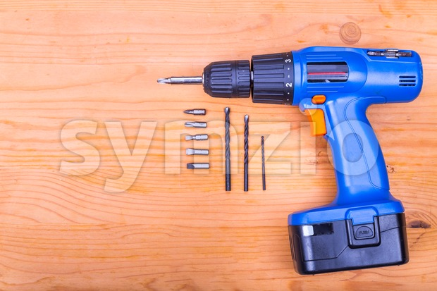 Flatbed of convenient cordless drill cum screwdriver set with bits on wooden background