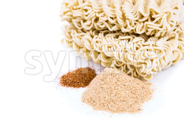 Unhealthy flavoring powder with uncooked instant noodles in background Stock Photo