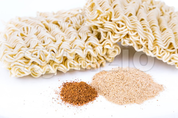 Unhealthy flavoring powder with uncooked instant noodles in backkground Stock Photo