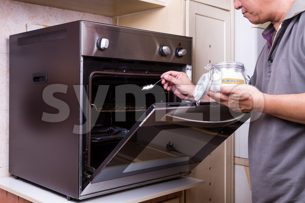 Person sprinkling baking soda into an oily oven as cleansing agent to clean