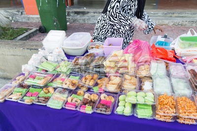 Vendor selling assorted Malay sweet cakes food at street stall Stock Photo