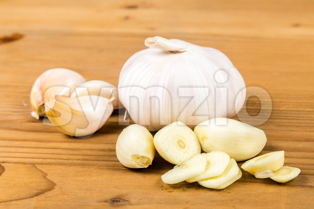 Peeled and sliced garlic cloves with whole garlic bulb and cloves as background Stock Photo