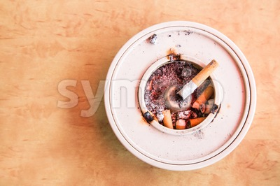 Overhead view of cigarette butts in ashtray placed on table Stock Photo