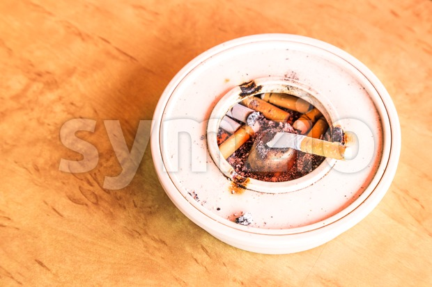 Cigarette butts in ashtray placed on table with natural light Stock Photo