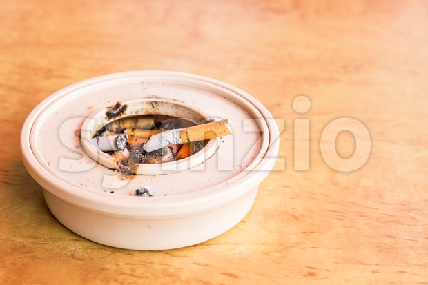 Cigarette butts in ashtray placed on table flushed left Stock Photo