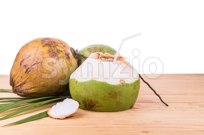 Three refreshing green organic coconut fruit juice on wooden table Stock Photo