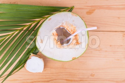 Refreshing green organic coconut fruit juice on wooden table Stock Photo