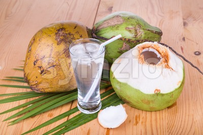 Three refreshing green coconut fruit juice in glass on wooden table Stock Photo