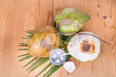 Refreshing green coconut fruit juice in glass on wooden table Stock Photo