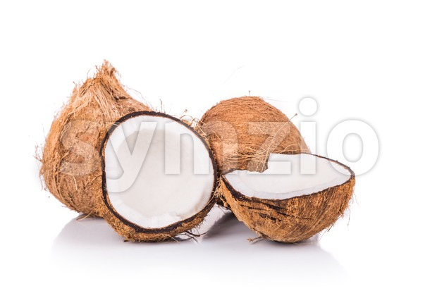 Old brown organic coconut fruits with one broken into half Stock Photo