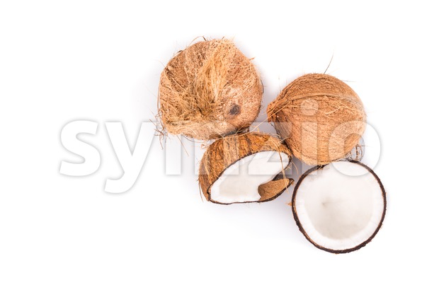 Overhead view of old brown organic coconut fruits with one broken into half on white background