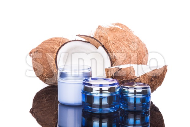 Closeup on coconuts and three tubs containing coconut oil used as natural moisturizer in skincare