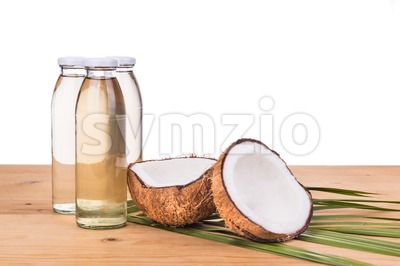 Cold pressed extra virgin coconut oil in bottles with coconuts Stock Photo