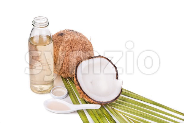 Cold pressed extra virgin coconut oil in bottles with coconut fruits in white background
