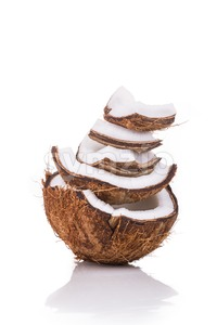 Old brown organic coconut fruit broken into pieces and stacked Stock Photo