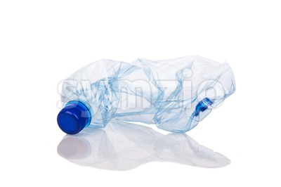 Mineral water bottle crushed and crumpled against white background Stock Photo