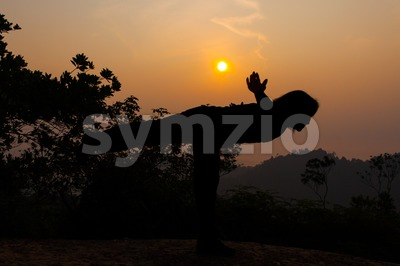 Women yoga pose in silhouette on hill summit during sunrise Stock Photo