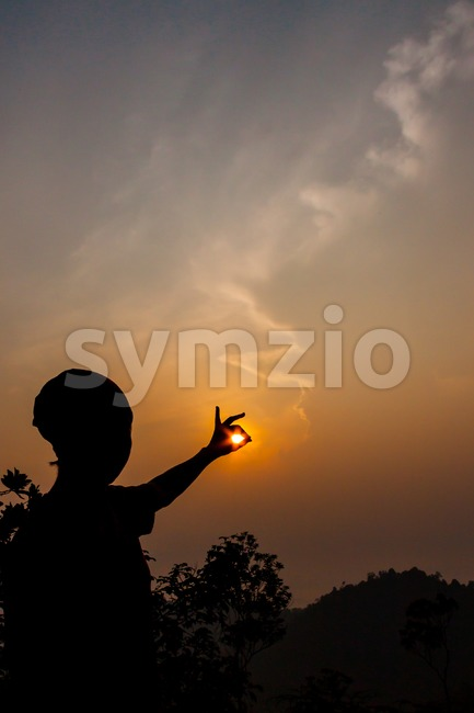 Silhouette of women catching sun with her fingers during sunrise Stock Photo