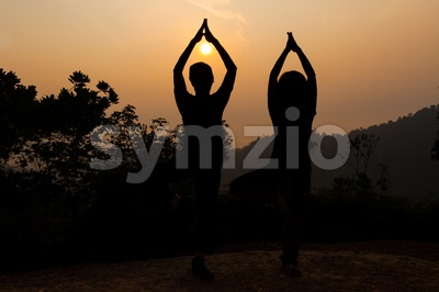Two women doing yoga tree pose in silhouette during sunrise Stock Photo