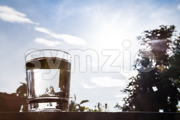 Silhouette of water in transparent glass against sky and sun Stock Photo