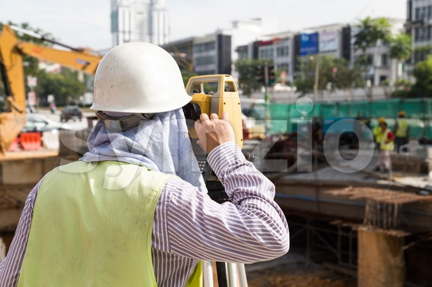 Engineer operating the dumpy automatic level instrument at construction site Stock Photo