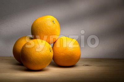 Four fresh oranges on wooden table with rays of light Stock Photo