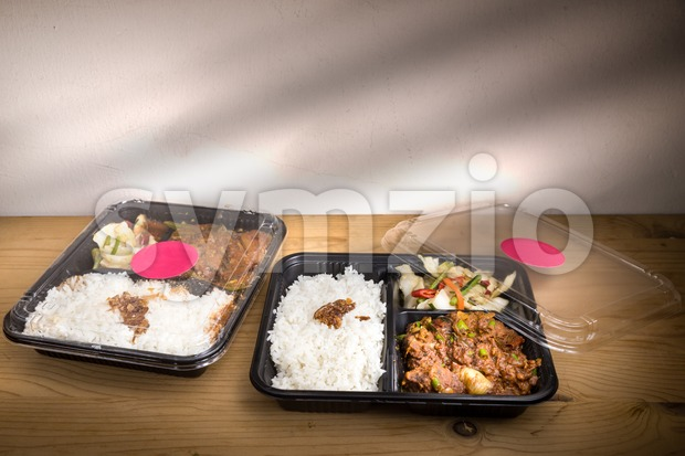 Two convenient take-away meal boxes with rice, meat and vegetable on wooden table top
