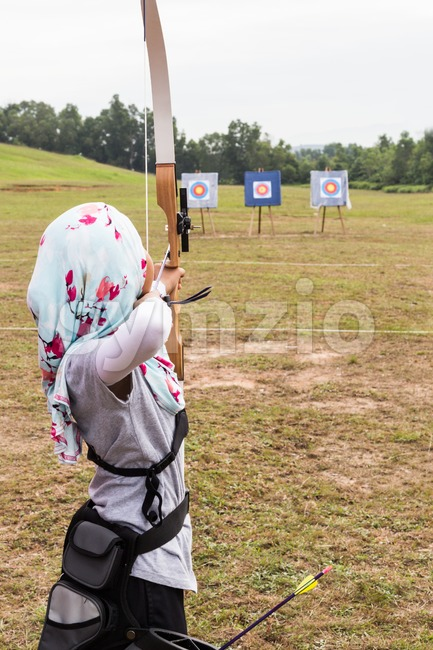 Person practicing at outdoor archery target range, aiming at target board