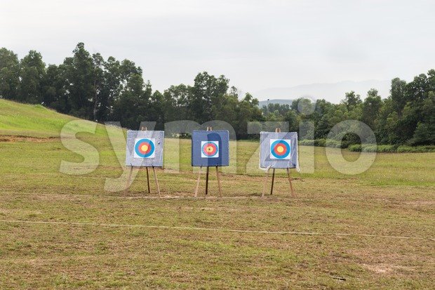 Outdoor archery target range with three target boards against serene background