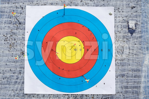 Closeup on outdoor archery target board with arrow on bullseye Stock Photo