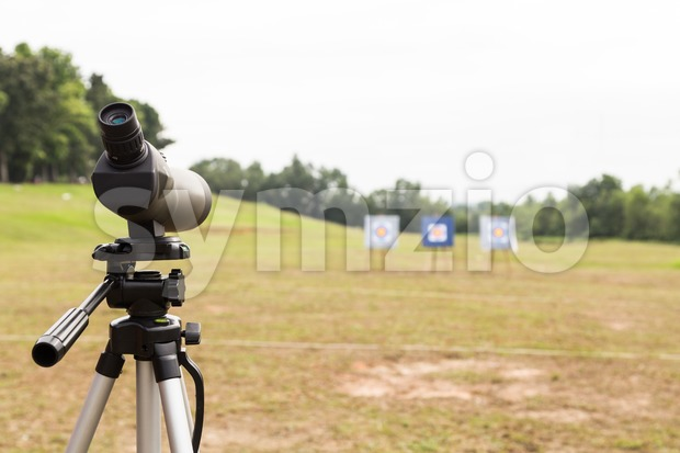 Spotting scope on tripod at outdoor archery target range Stock Photo