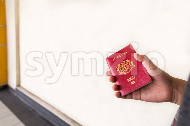 Hand holding Malaysia international passport against wall background Stock Photo