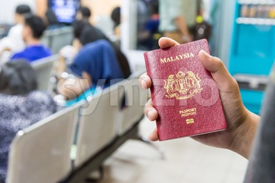 Hand holding Malaysia international  passport against bokeh crowd background Stock Photo