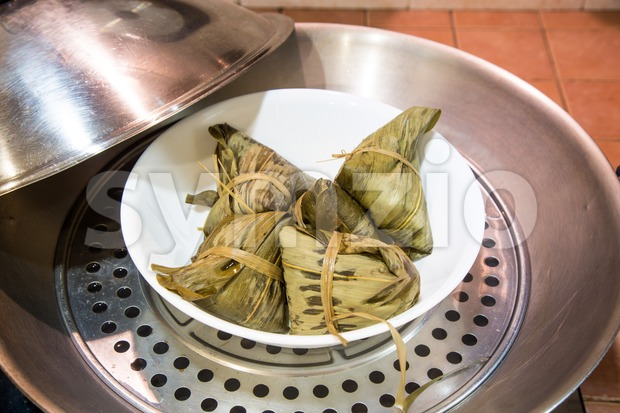 Chinese rice dumplings or zongzi in wok for steaming Stock Photo
