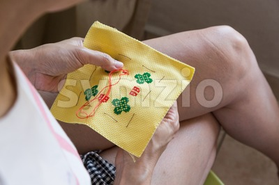 Closeup on person embroidering cross stitch with needle and thread Stock Photo