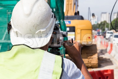 Surveyor operating the dumpy automatic level instrument at construction site Stock Photo