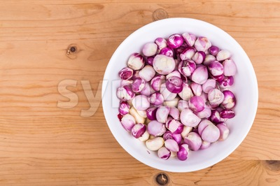 Bowl of peeled shallots onion and garlic on wooden table Stock Photo