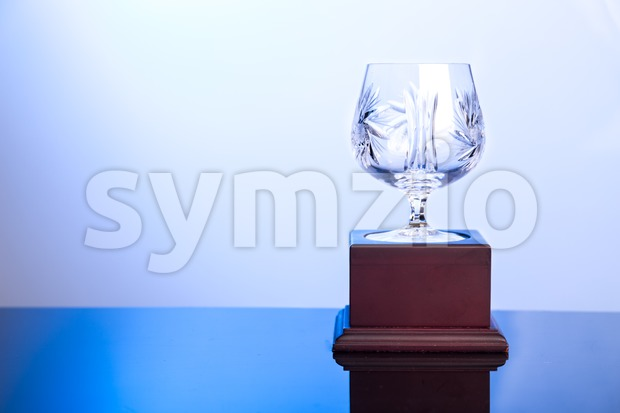 Elegant crystal cup trophy on blue hue ambient Stock Photo