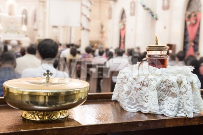 Catholics bread and wine in chalice with mass in background Stock Photo