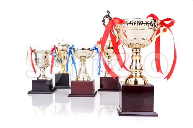Group of elegant gold trophies with decorative ribbons, with focus on one on foreground