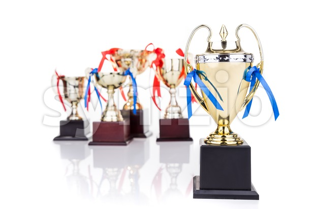 Group of gold trophies with decorative ribbons, focusing on one Stock Photo