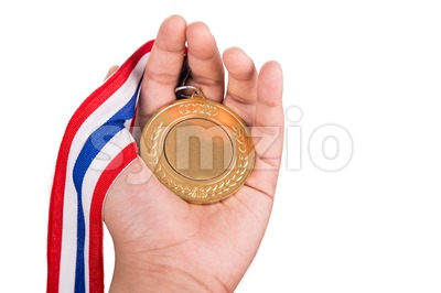Athlete holding gold medal with ribbon on his hand Stock Photo