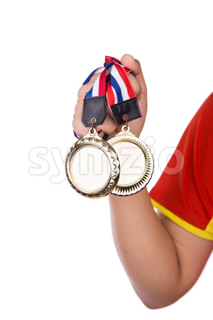 Athlete holding gold medals with ribbon with his hand, against white background