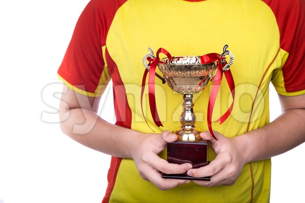 Athlete holding gold trophy with both hands against white background