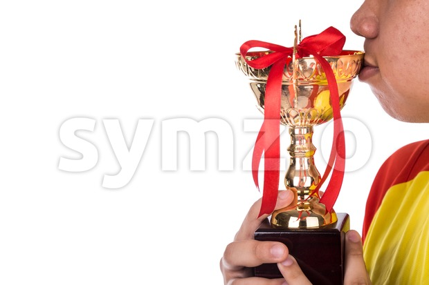 Athlete holding and kissing on gold trophy against white background
