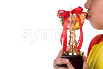 Athlete holding and kissing on gold trophy Stock Photo