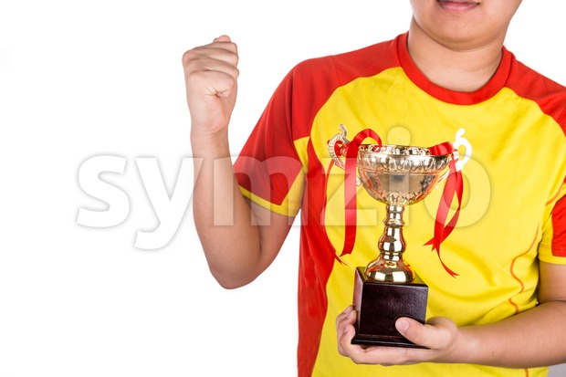 Proud athlete gestures with firm fist whilst holding gold trophy, against white background