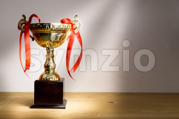 Elegant gold trophy with red decorative ribbons on wooden table with ray of light.  Fine art rendition.